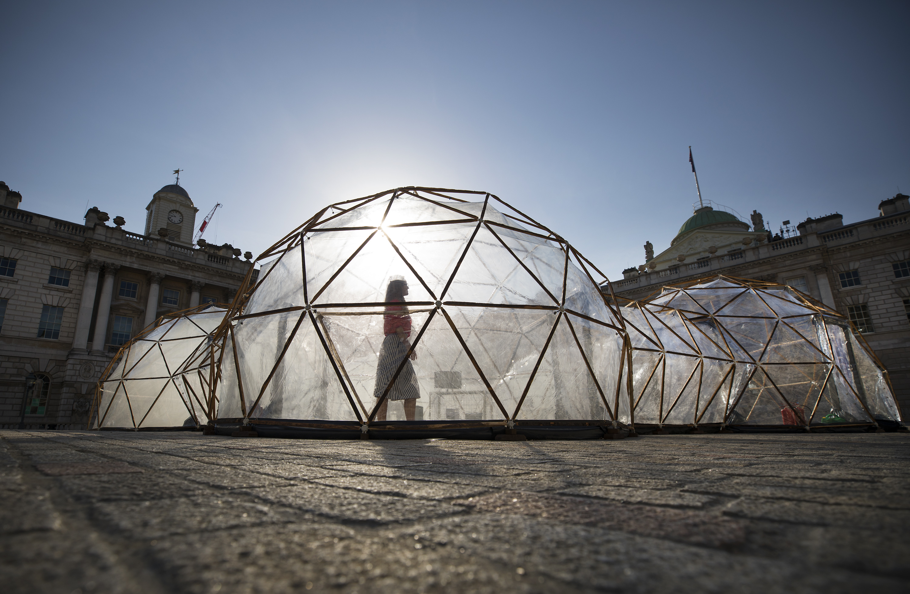 18/04/2018. London, UK. Visitors walk through British artist Michael Pinsky's Pollution Pods, a new sensory work, installed in the courtyard at Somerset House in London to mark Earth Day 2018. A series of five connecting domes recreate the pollution from London, Beijing, São Paulo, New Delhi and Tautra in Norway. Visitors are invited to experience first-hand the difference in the air quality of global environments. The Pollution Pods are open until 25th April 2018, including Earth Day on the 22nd April. Photo credit: Peter Macdiarmid