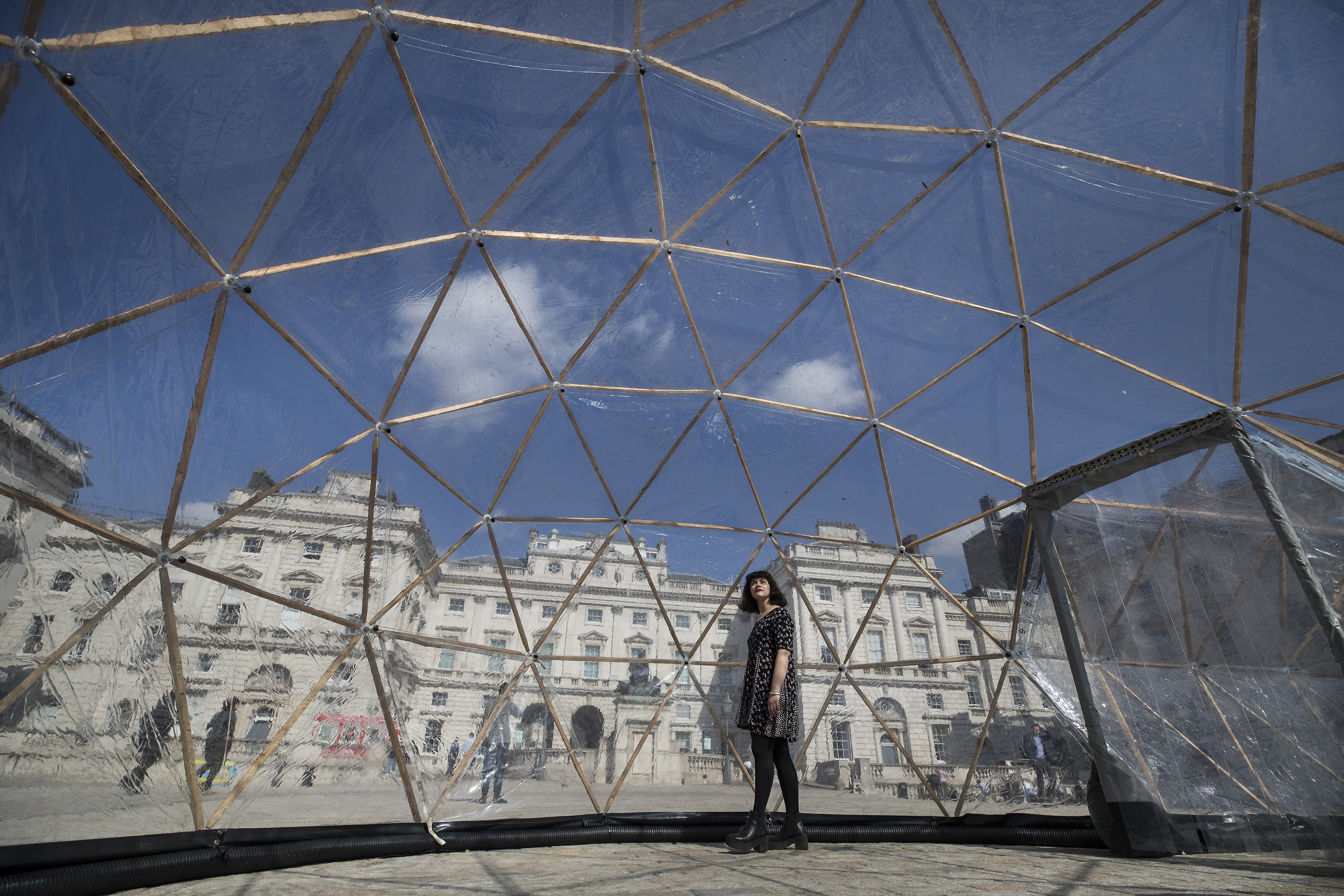 18/04/2018. London, UK. A visitor walks through one of British artist Michael Pinsky's Pollution Pods, a new sensory work installed in the courtyard at Somerset House in London to mark Earth Day 2018. A series of five connecting domes recreate the pollution from London, Beijing, São Paulo, New Delhi and Tautra in Norway. Visitors are invited to experience first-hand the difference in the air quality of global environments. The Pollution Pods are open until 25th April 2018, including Earth Day on the 22nd April. Photo credit: Peter Macdiarmid/Somerset House